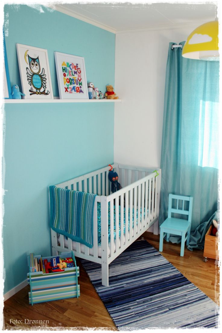 Nursery/kid's room in white, teal and yellow. Toybox with stripes from SEBRA. Chair and lamp from IKEA.