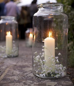 Candles in jars to light tables and pathways at a wedding.