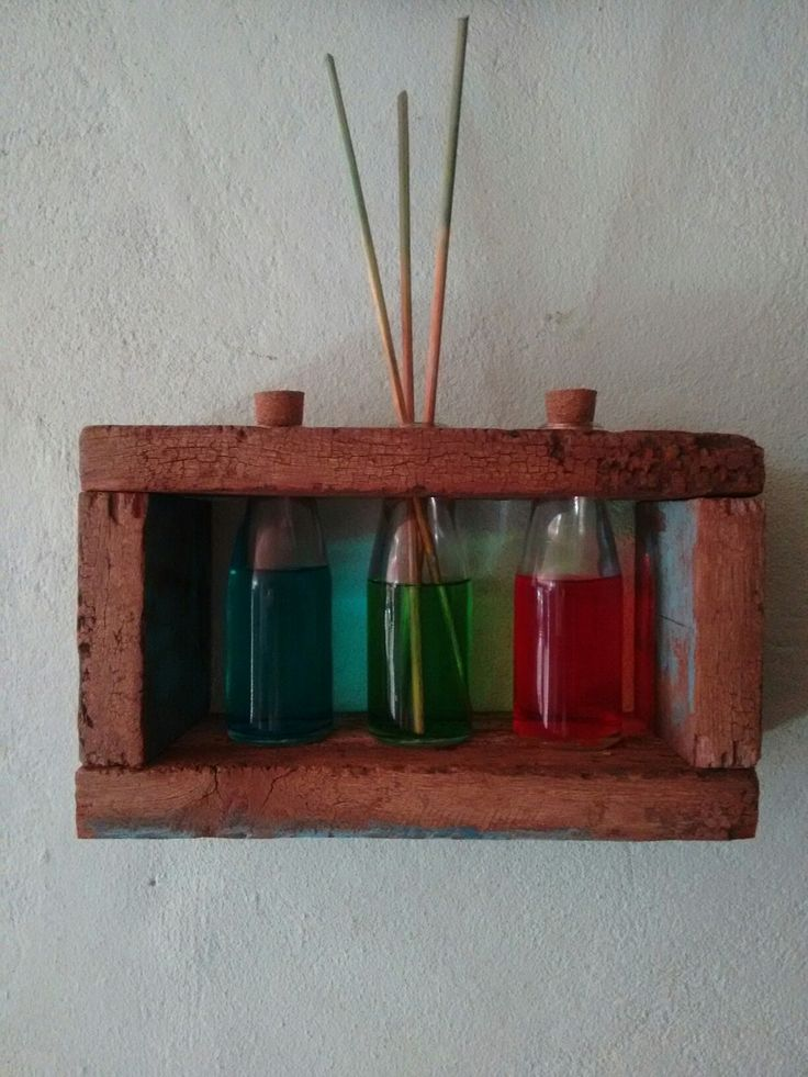 Pequeno enfeite feito com tábuas velhas e garrafinhas com aromatizadores de ambientes de diferentes cores e fragrâncias. Inspiração dos DIY feitos de paletes.