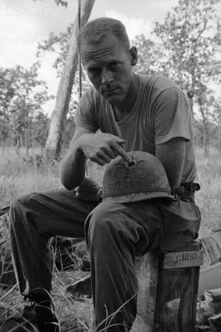 "John Wiest, of the U.S. 1st Cavalry, shows where a Viet Cong bullet pierced his steel helmet while pinned down by Communist fire near Plei Me, November 6th. Wiest told newsmen, ""All I got was a headache"". (November 8, 1965)"