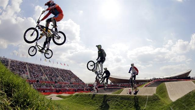 BMX Takeoff:   Raymon van der Biezen of the Netherlands and Australia's Khalen Young (front and back on L) jump during their men's BMX quarter-final run during the London 2012 Olympic Games (Reuters)