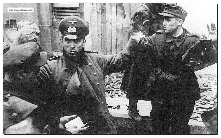 HISTORY IN IMAGES: Pictures Of War, History , WW2: Apocalypse: Battle Of Berlin: 1945  A Russian soldier checks the papers of German soldiers.