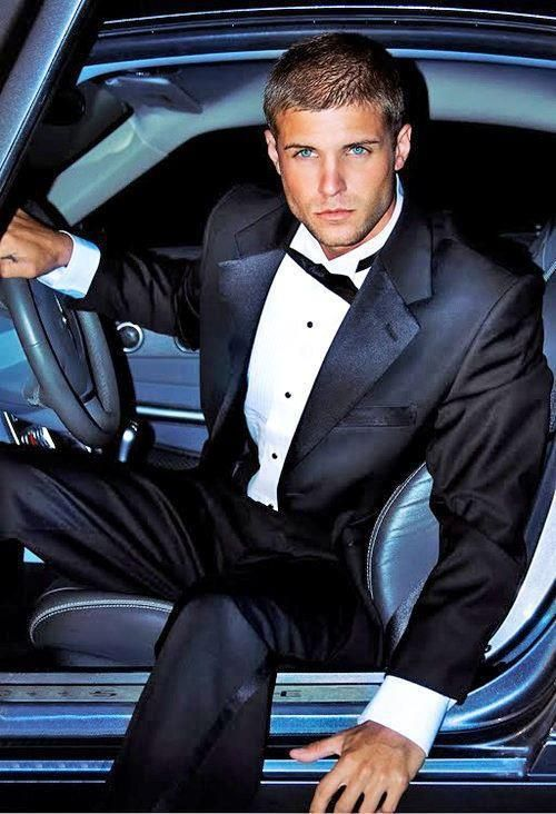 Hunky male model wearing tuxedo and getting out of his car ...