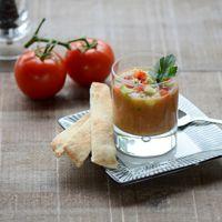 Breng een pan met ruim water en zout aan de kook. Snijdt het groene kroontje uit de biologische tomaten en snijd aan de bovenzijde de tomaten kruislings in