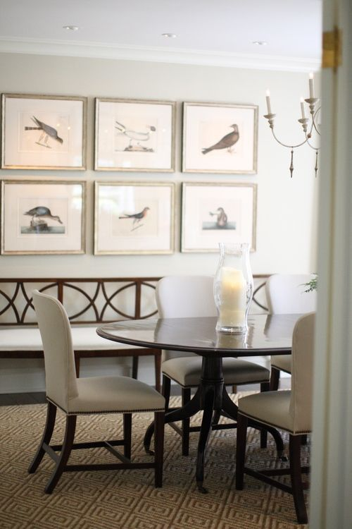 The colors and beautiful gallery wall of bird paintings bring a natural touch to this new traditional dining room without the introduction of rustic