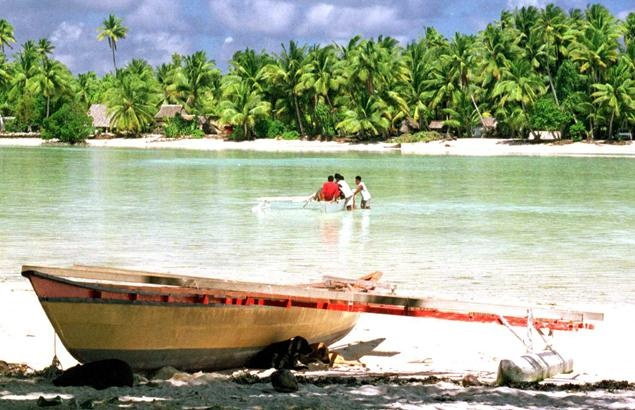 TARAWA, KIRIBATI - JUNE 11:  A traditional Micronesian canoe sits on the shore, 05 June 1999, as people cross a lagoon on an atoll of Tarawa in the central Pacific's Kiribati. Although Tarawa is one of the world's most densely populated places the canoe sits on a relatively deserted beach on north Tarawa.  (Photo credit should read MICHAEL J. FIELD/AFP/Getty Images)