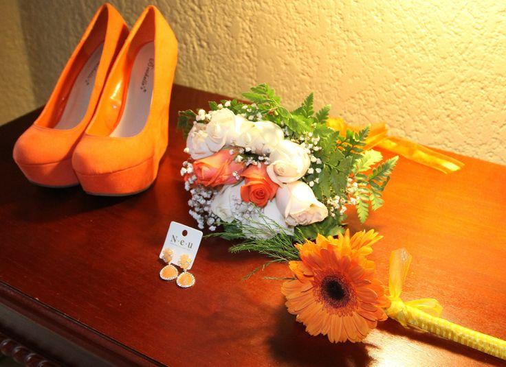 Los accesorios : zapatos naranjas, bouquet naranja con blanco, los aretes naranja.