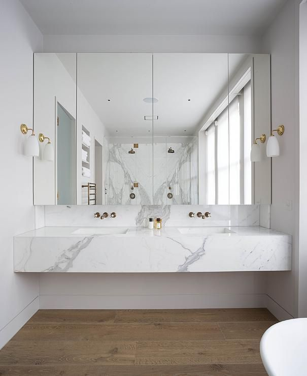 Modern bathroom features a floating marble vanity fitted with his and her sinks and gold faucets under mirrored medicine cabinets illuminated by white glass and gold sconces.