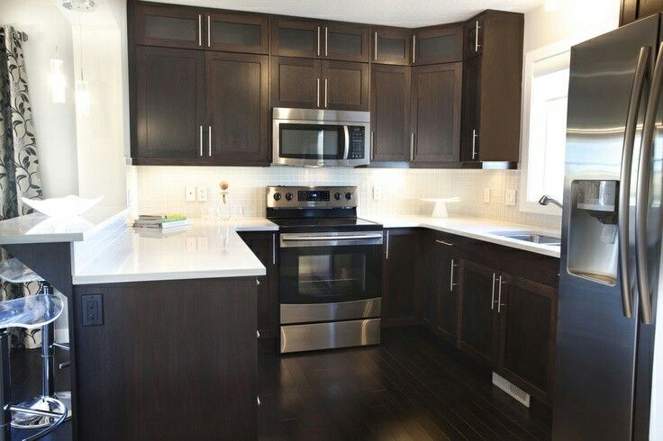 White quartz counters with dark brown cabinets and floor ...
