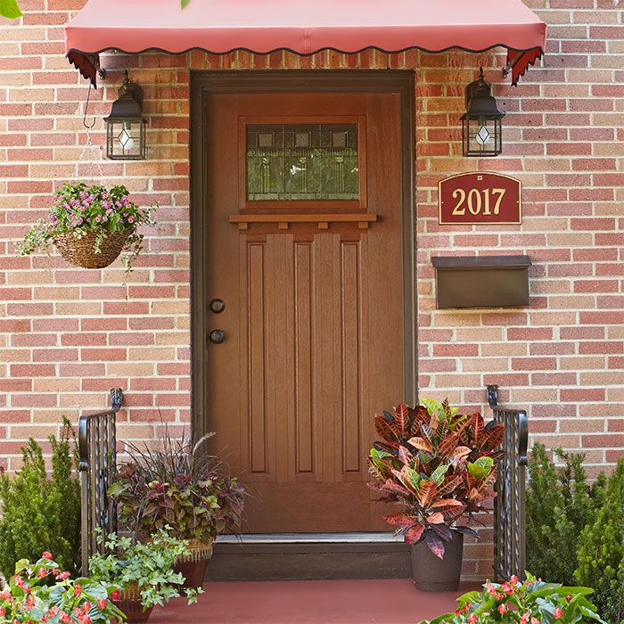 Front porch with house numbers beneath a wall mounted porch light