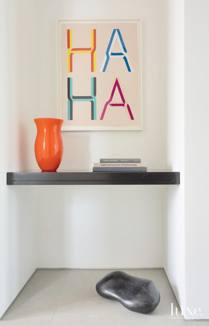 Tucked just outside the owners' study on the main level is the playful painting HA HA by Tauba Auerbach. The shelf is custom by Jennifer Post Design.