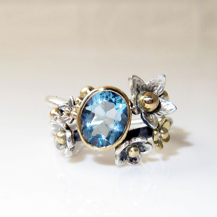 The topaz is blue as the sky and deep as the ocean. The ring is made of silver. A belt of gold lies around the ropaz creating a warm contrast to the cold stone.