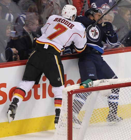 Calgary Flames at Winnipeg Jets - Game W 5-4 SO- 11/18/2013 TJ Brodie #7 of the Calgary Flames and Evander Kane #9 of the Winnipeg Jets collide behind the Calgary at MTS Centre in Winnipeg, Manitoba, Canada. (Photo by Marianne Helm/Getty Images)