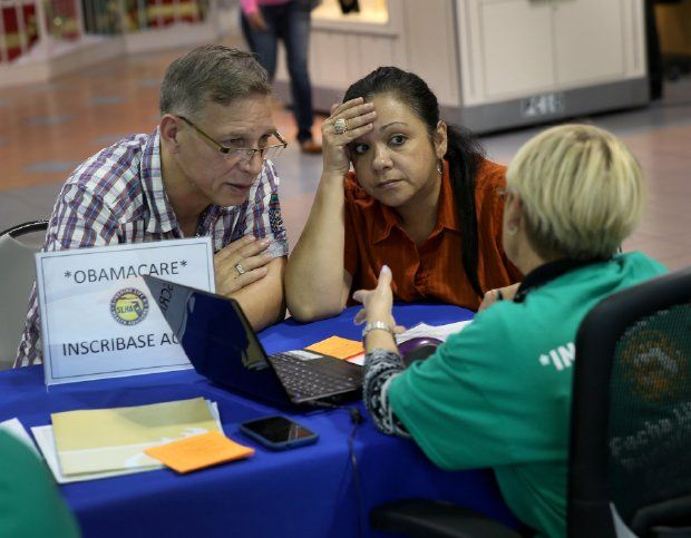 Angel Rivera (L) and his wife Wilma Rivera sit with, Amada cantera, an insurance agent with Sunshine Life and Health Advisors as they try to purchase health insurance under the Affordable Care Act at the kiosk setup at the Mall of Americas on December 22, 2013 in Miami, Florida. (Photo by Joe Raedle/Getty Images)