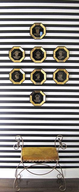 Narrow black & white stripes, gold hexagon frames, and antique stool.
