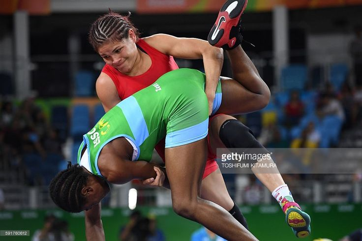 Venezuela's Betzabeth Angelica Arguello Villegas (red) wrestles Cameroon's Joseph Emilienne Essombe Tiako (blue/green) in their women's 53kg qualifying match on August 18, 2016, during the wrestling event of the Rio 2016 Olympic Games at the Carioca Arena 2 in Rio de Janeiro. / AFP / Toshifumi KITAMURA