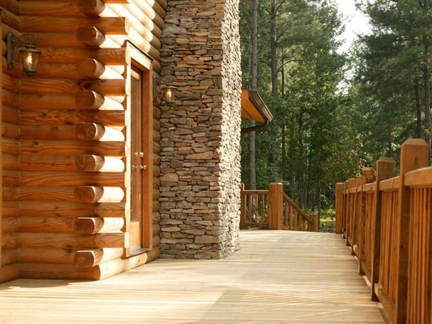 """Designer Decks  Made From Natural Wood, Composite and Aluminum : The natural-wood deck is stained lighter to contrast with the cabin's logs and railings. The colors play off the stone fireplace, enhancing the classic """"pioneer era"""" architecture.  Photo by Southland Log Homes. From DIYnetwork.com"""