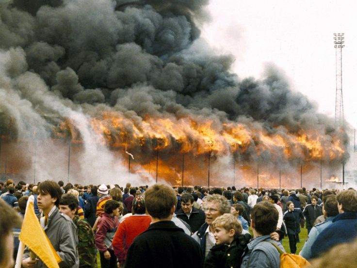 Crowds on the pitch at Valley Parade stadium after the stand caught fire on 11 May 1985. The disaster killed 56 supporters