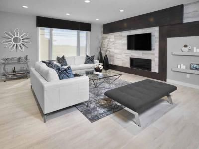 """Tile combined with dark wood """"panels"""" make a stunning statement around the fireplace in this home. In the Onyx model by Kimberley Homes, Edmonton, Alberta  #fireplace #greatroom #livingroom #bonusroom  #interiordesign #newhomedesign #homedesign #newhome #customhome #yegre #buildwithkimberley #kimberleyhomes"""