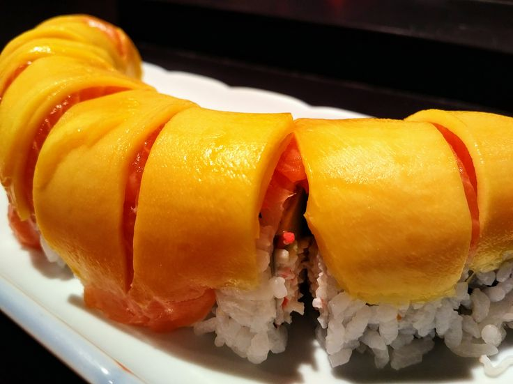 Mango Salmon Roll -Immitation crab meat and avocado topped with salmon and mango.