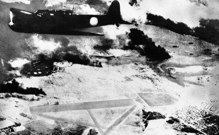 A Japanese bomber on a run over Pearl Harbor, Hawaii is shown during the surprise attack of Dec. 7, 1941. Black smoke rises from American sh...