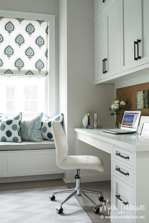 Chic home office features cabinets and a framed cork board placed over a white built-in desk paired with a white leather tufted chair on wheels.