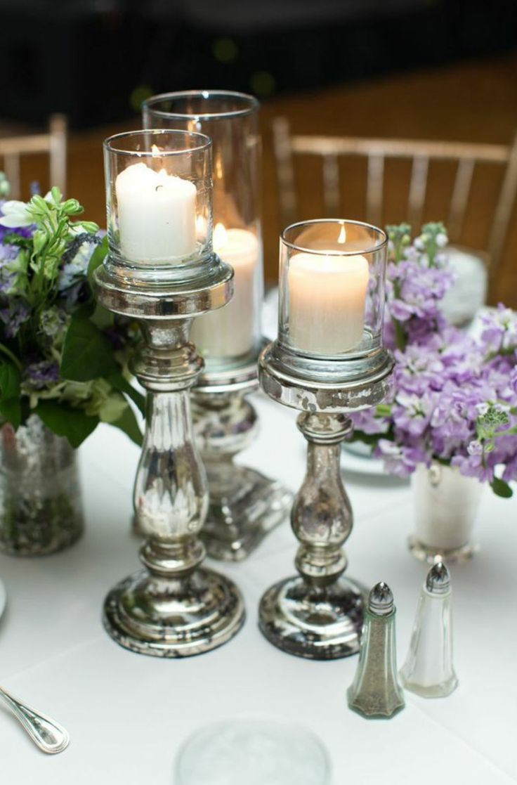 a trio of mercury class pedestals topped with pillar candles adds a warm and festive element to the table centerpiece