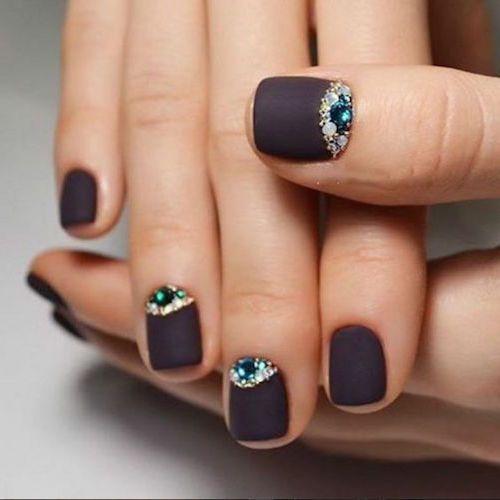 Una delicadeza de diseño de uñas cortas en negro matte con incrustaciones de joyas.