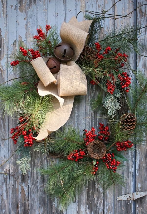 Natural style wreath: greenery, berries, pine cones, a burlap bow and bronze jingle bells
