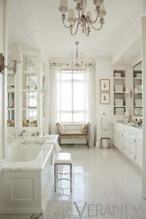 I think I'm always all about a bathroom decorated like a toile circus and then I see an all-white stunner like this master bath by Thomas O'Brien. No color needed as white paint, mirrors, silver light fixtures, Carrara marble, and shimmering floor tile make quite the visual impact. Two framed prints on the far wall, sheer drapes, and tiny velvet settee beneath the window personalize the space.