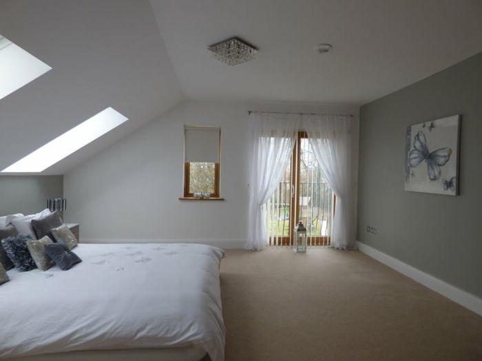 dormitorio abuhardillado, colores habitación claros, cuadro decorativo con mariposa, cama matrimonio en blanco