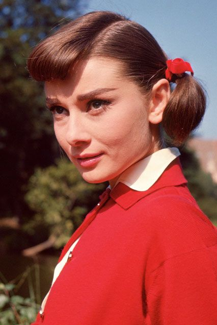 1957 - For Love in the Afternoon, Hepburn sported girlish pigtails tied with cherry red ribbons.