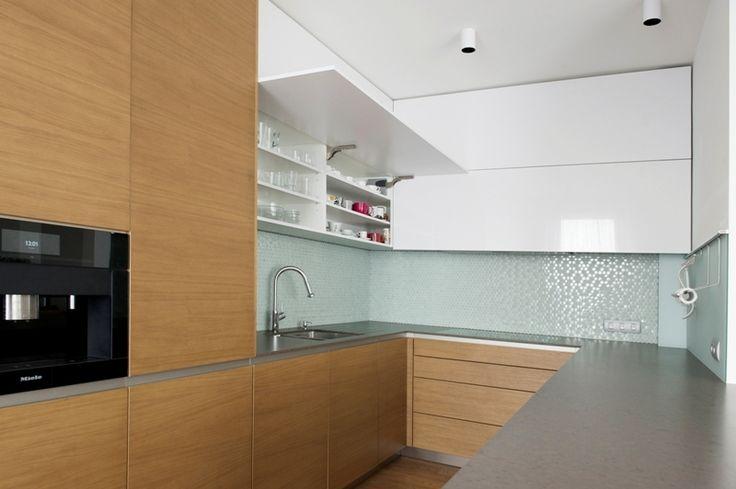 Horné skrinky kuchynskej linky prakticky využívajú steny až po strop. Biele lakované dvierka kút opticky odľahčujú. Na oživenie čistých plôch použili dizajnérky sklenenú mozaiku, ktorá pôsobí ešte efektnejšie pri zapnutom LED podsvietení.