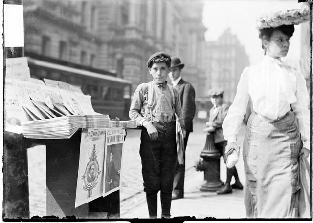 [Newsboy holding newspapers and standing next to a paper stand on a commercial street]