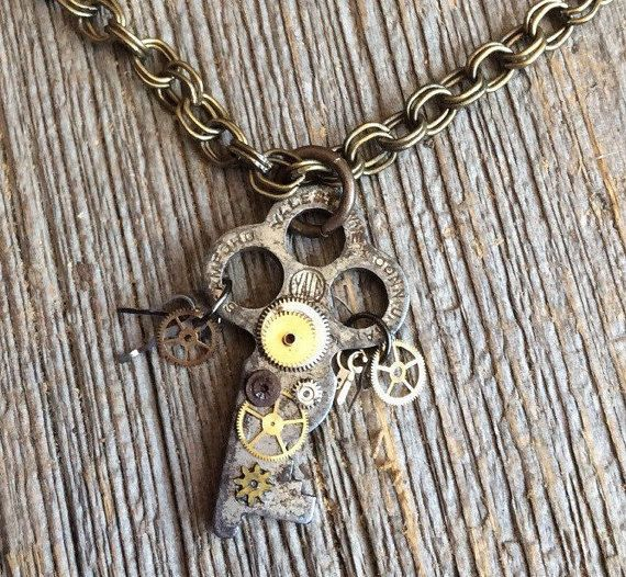 This unique one of a kind necklace is made with a vintage key. Attached are old watch gears. Some are glued on while others dangle from each side. The