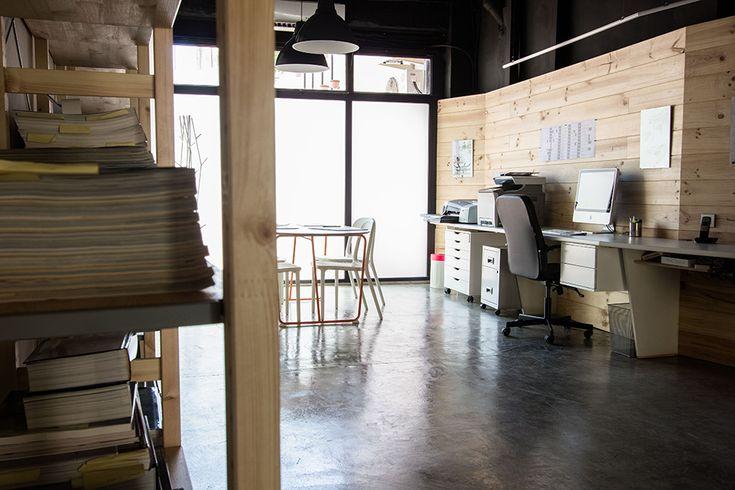 Chiralt Arquitectos I Mobiliario minimalista en oficina moderna con suelo pulido de hormigón visto. Mampara traslúcida a patio interior.