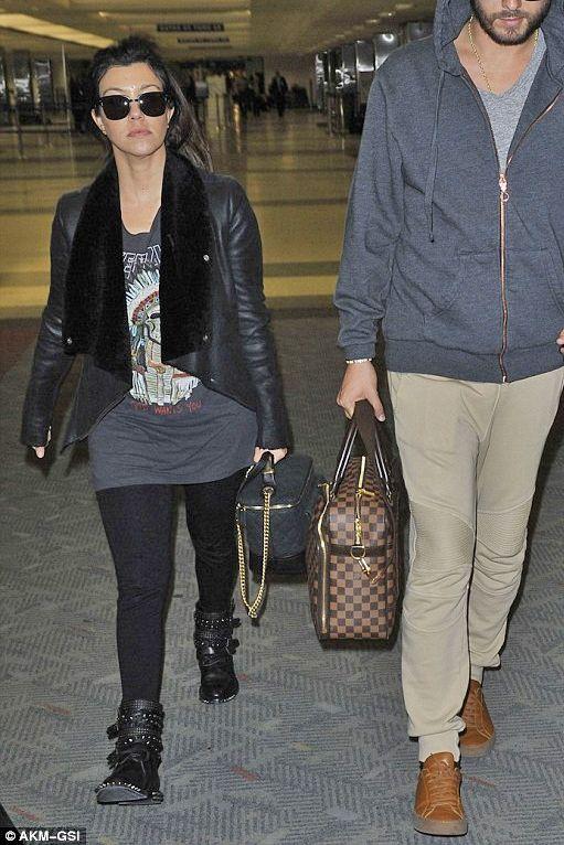 Kourtney Kardashian wearing Saint Laurent Signature Rangers studded Leather Boots Chanel Globe Trotter Vanity Bag Yeezus Tour Merch Indian Chief T-Shirt