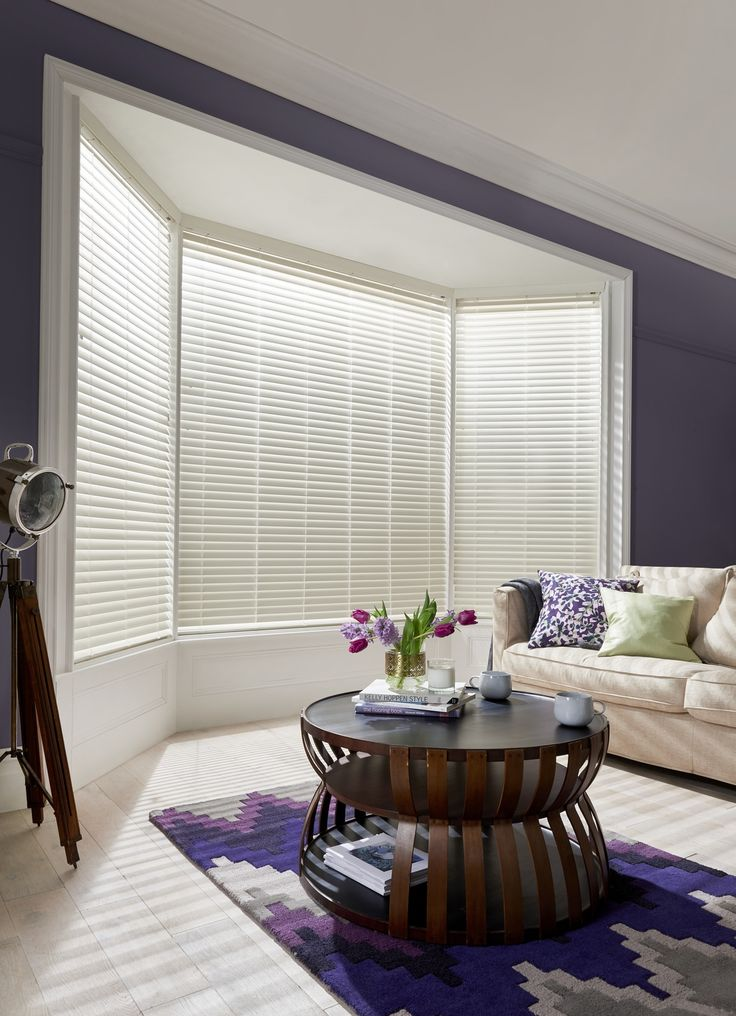 Create a light and spacious feel with beautiful made-to-measure Bone White Faux Wood blinds. In this sultry living room, the creamy tones stand out against the inky walls and lend real warmth to this elegant scheme