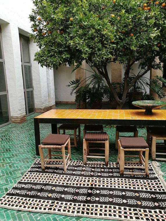 Voormalige Berber tapijt van de hoge Marokkaanse Atlas Azilal.  Deze matten zijn werken van volkskunst die vergelijkbaar zijn met schilderijen. Ze zijn met de hand gemaakt door vrouwen die originele en unieke patronen maken.  Tapijten gemaakt van natuurlijke wol.  Uniek model. 200 cm x 120 cm ca.  Natuurlijke kleuren: zwart, beige, rood/geel/oranje.