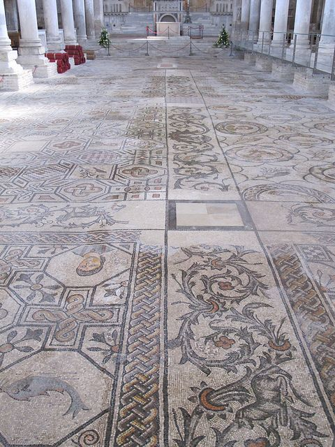 aquileia, Italy. To protect these mosaic floors, there is a layer of thick glass or plexiglass suspended over the top of the floor.