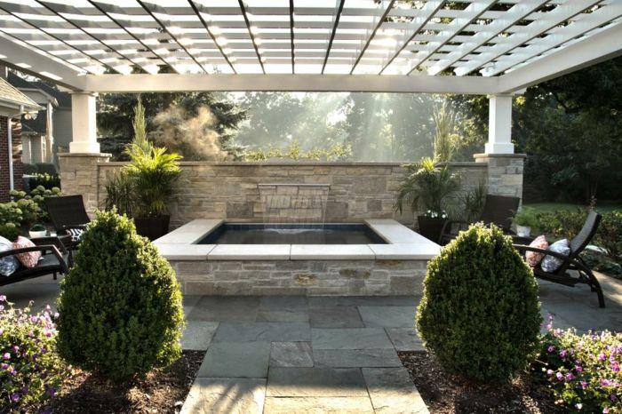 piscine hors sol rectangulaire en pierre, cascade d'eau, pergola en bois