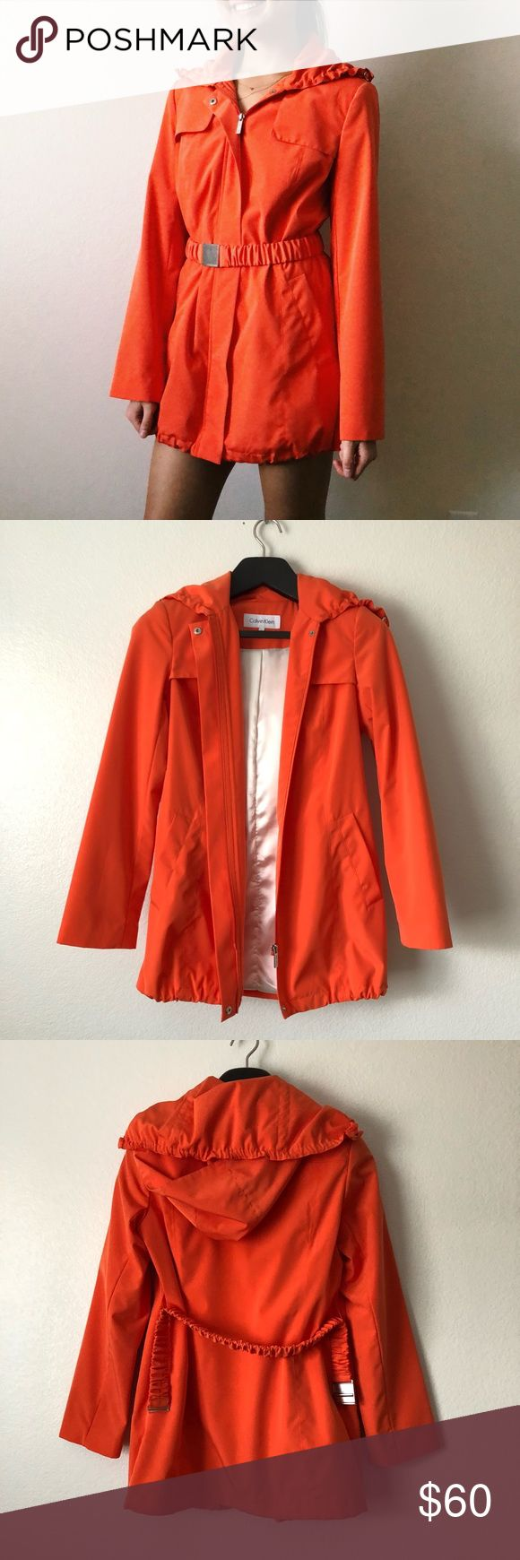 "Calvin Klein Sleek Orange Zip Up Trench Coat Calvin Klein Sleek Orange Zip Up Trench Coat   -Super trendy, unique, fashionable! -Vibrant Orange, removable hoodie, longsleeves, satin inside, elastic removable belt, drawstring on bottom of coat, light shoulder padding  -Pristine overall Condition, some wear on belt buckle  -Measurements (all approx.) Shoulders: 16""Chest: 38"" Waist: 34""Length: 3""Sleeves: 24""  -Smoke free home, ask all questions before purchasing IG: @ jadeskelton_ Calvin Klein…"