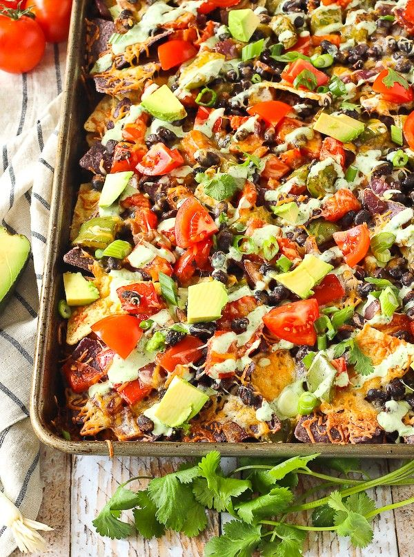 Words cannot express how badly you need these vegetarian nachos in your life. They're great on their own but the creamy cilantro lime drizzle puts them over the top! Get the recipe on RachelCooks.com! #sponsored @MilkMeansMore