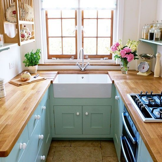 Lovely small horseshoe kitchen layout with aqua cabinets and wood countertops and a view over the sink, via House to Home | Tiny Homes