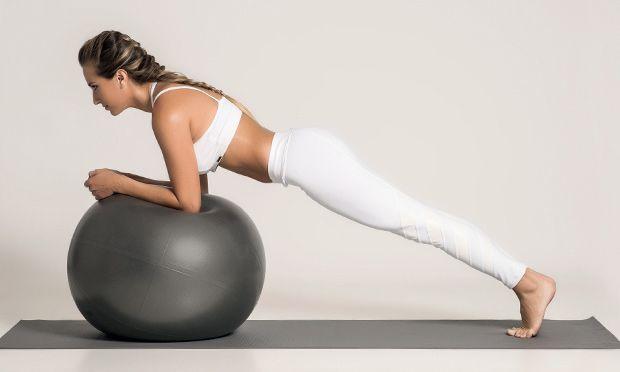 De bruços, com os antebraços apoiados na bola, pernas estendidas e ponta dos pés apoiada. O corpo deve formar uma linha diagonal, com o peito aberto e os cotovelos formando um ângulo de 90 graus. Sustente a posição durante 10 respirações.