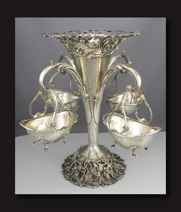 American sterling silver epergne with center trumpet vase with a cast ornate floral base and rim. The trumpet is hand engraved with scrolls and flowers. The four hanging footed baskets are hand engraved with the same motifs and hang from four arms. The vase and baskets have script monograms. Maker is Roger Williams of Providence, RI.