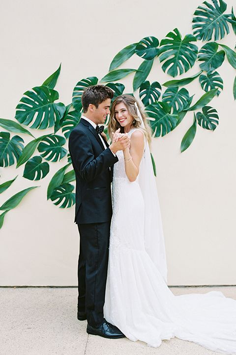San diego wedding shoot at estancia hotel bride a line gown with lace bodice and chiffon with thick straps and pluning neckline with long headpiece decor for hair and groom black tuxedo with white dress shirt and black and white polka dot bow tie