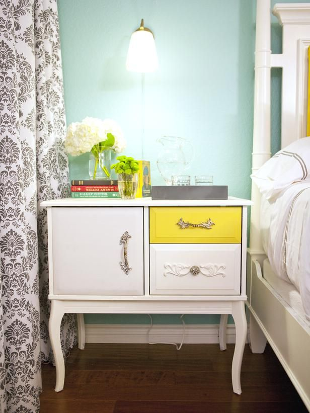 small dresser is repurposed as a cool, eclectic nightstand. One drawer is painted a bright yellow for a burst of color and different knobs are used to give the piece a one-of-a-kind look.