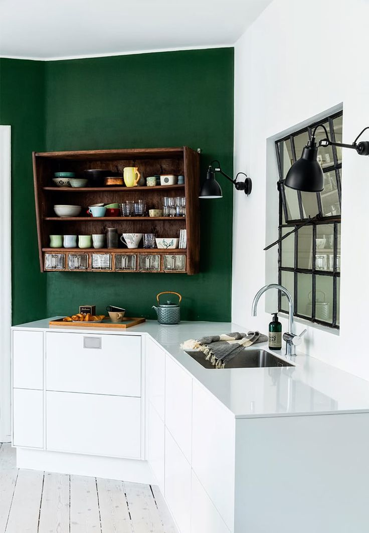 The simple white kitchen has been given life and charm with raw wall lamps from La Lampe Gras, a barn window, bottle green wall and a vintage kitchen cabinet that has been stained brown.
