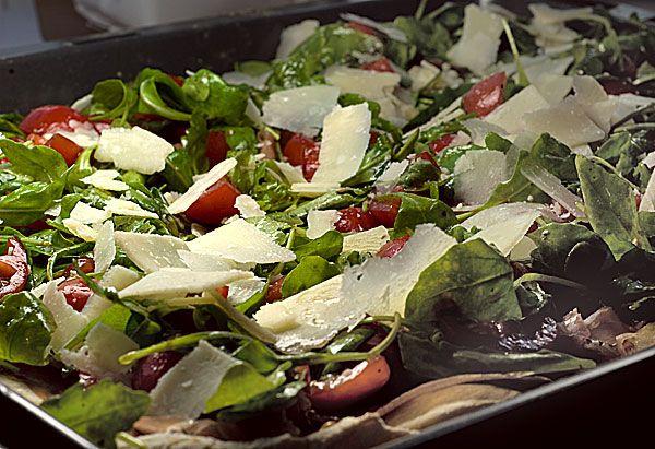Pizza mit Rucola, Schinken und Tomaten